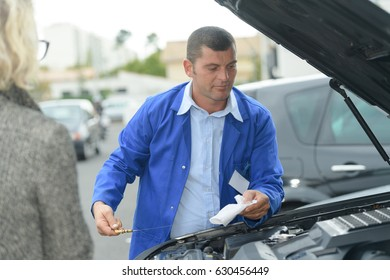 mature mechanic fixing a car engine in his garage