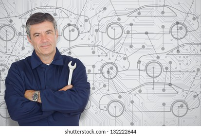 Mature mechanic standing in front of a cars diagram background while looking at camera