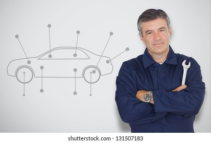 Mature mechanic standing next to car diagram while looking at camera
