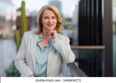 Mature middle aged therapist psychologist type professional female in a business suit standing outside office