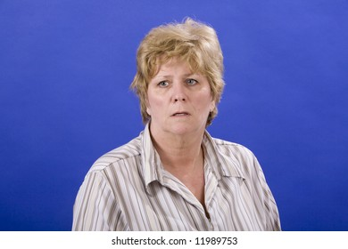 mature middle aged woman worried on a blue back ground