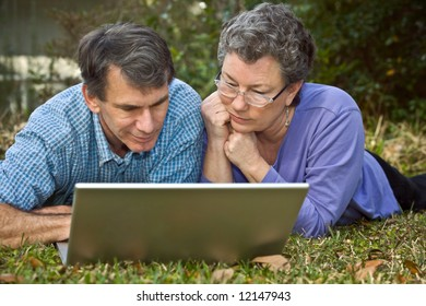Mature middle-age couple lying in the grass and surfing the web on their laptop.