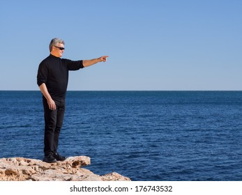 Mature middle-aged man standing on a rock at the coast pointing towards copy space over a calm blue ocean on a sunny day