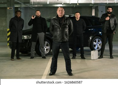 Mature mixed-race gangster or criminal authority in black leather jacket and jeans standing in front of his gang on parking area