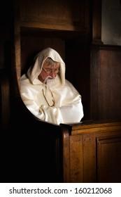 Mature monk sitting in a dark medieval church