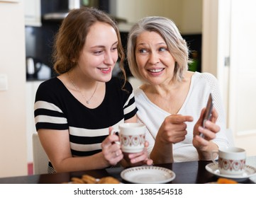 Mature mother with adult daughter sitting with smartphone in kitchen interior