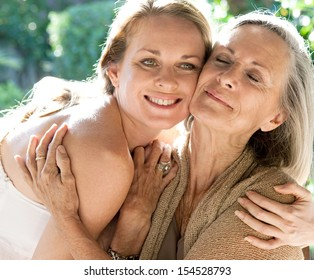 Mature mother and adult daughter spending time together in a home garden hugging tightly and affectionately cuddling during a bright and golden summer sunny day outdoors.