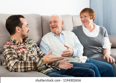 Mature mother and father and son happy to spend time together at home