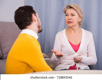 Mature mother having disagreement with adult son at home