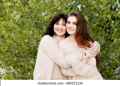 Mature mother hugging with her teen daughter outdoor in nature on sunny day. Fall fashion, warm sweaters