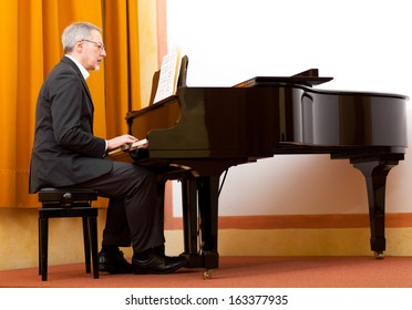 MAture musician playing the grand piano