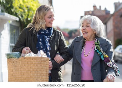 Mature Neighbor Helping Senior Woman To Carry Shopping