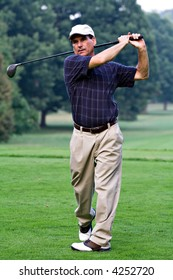 Mature nicely dressed man finishes swing after hitting golf ball with driver.