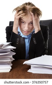 mature office worker holds her head in her hands at the thought of the paperwork infront of her.