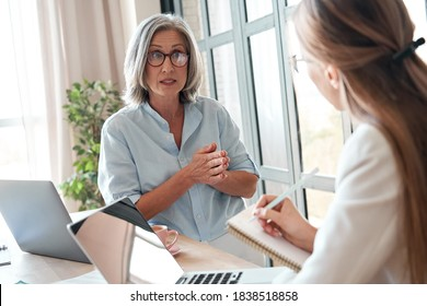Mature old female mentor or manager training young intern explaining sharing professional skills in office. Middle aged senior business woman teacher speaking to student teaching trainee at meeting.
