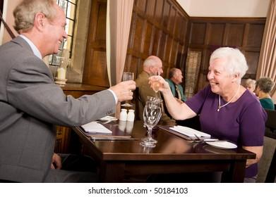 Mature older couples enjoying a celebration in a restaurant
