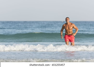 Mature older muscular fit Middle Eastern, Arab Male running out of the ocean on the beach, shirtless, wearing red shorts
