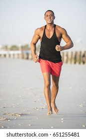 Mature older muscular fit Middle Eastern Arab Male running on the beach, wearing red shorts and a black muscle shirt