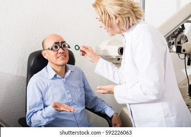 Mature optician doing eye check up to elderly smiling man