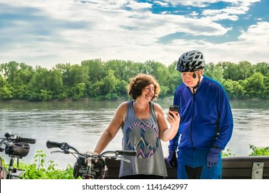 Mature overweight woman leaning on her bicycle shows something on her smart phone to a senior bicycle; Missouri River and the woods in the background