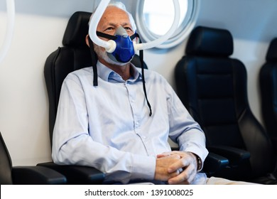 Mature patient breathing through oxygen mask during therapy in hyperbaric chamber at clinic.