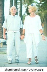 mature pensioners male and female walking in the park on holiday