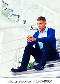 Mature pensive man sitting on stairs at home