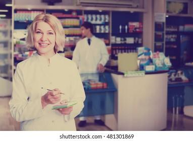 Mature pharmacist and pharmacy technician posing in pharmacy