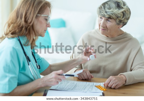 Mature physician prescribing medicament for elder woman