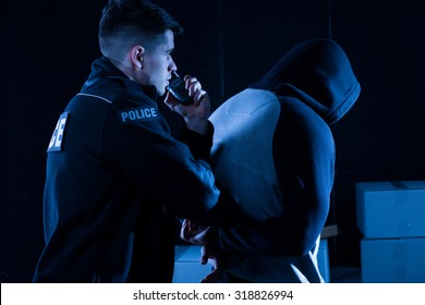 Mature policeman arresting law-breaker at night