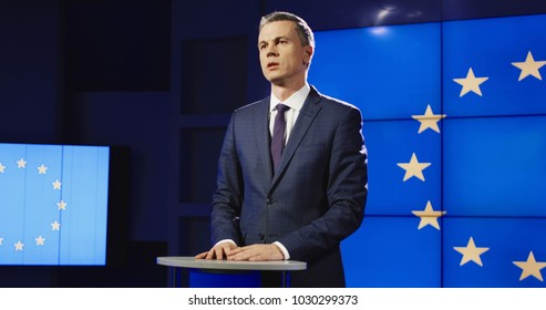 Mature politician in elegant suit standing on stage in light against screen with EU flag and giving speech while arranging press conference.