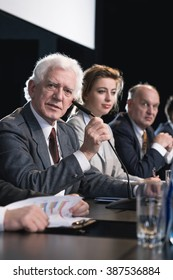 Mature politician and his election team during press conference
