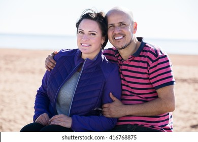 Mature positive couple sitting together on the bench and holding each other