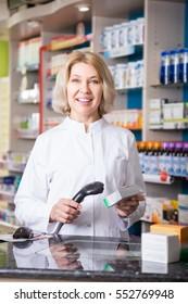 Mature positive female pharmacist posing in drugstore