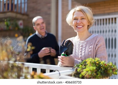 Mature positive female talking with male neighbor at balcon