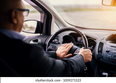 Mature professional elegant businessman in a suit is driving a car and honking.