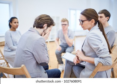 Mature psychologist looking at crying young businessman and trying to give him psychological help during session
