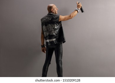 Mature punk in leather vest holding a spray for graffiti against a gray wall