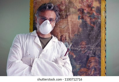mature restorer posing in studio with ancient painting artwork