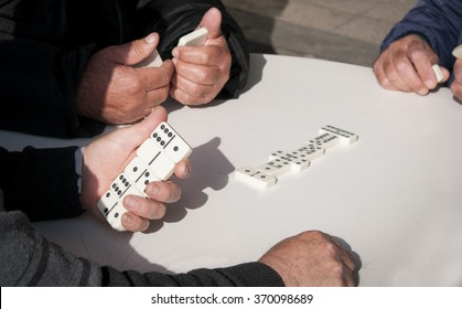 Mature retiree adults playing domino game for leisure