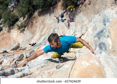 Mature Rock Climber taking the Hold on orange Mountain Wall high above ground