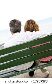 Mature romantic couple on a bench on seashore