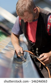 Mature roofer applying weld into the gutter parts to assemble it in a new construction site