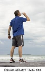 Mature runner drinking water on a beach