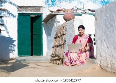 Mature Rural Woman using laptop at village.