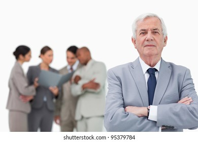 Mature salesman with arms folded and team behind him against a white background