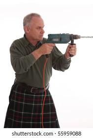 mature Scotsman in a Mackenzie kilt doing diy with a power drill