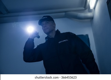 Mature security guard searching with flashlight in office building