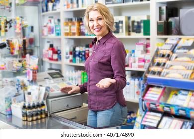 Mature seller at cash register desk in cosmetic shop