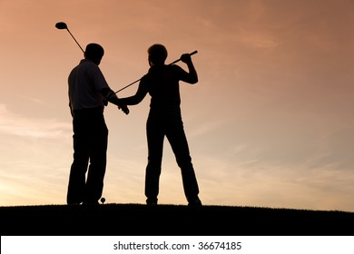 Mature or senior couple playing golf - pictured as a silhouette against an evening sky
